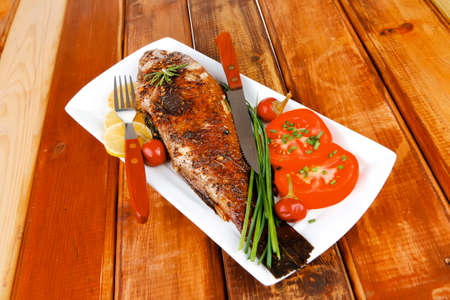 served main course on wood: whole fried seabass on plate with lemons,tomatoes and peppers Stock Photo