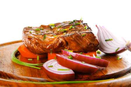 served roasted beef fillet with tomato on wooden dish