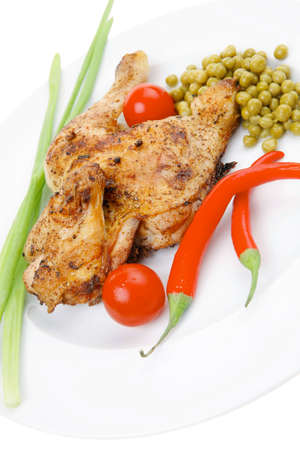 fine legs: meat food : roast chicken garnished with green onion and red chili hot pepper on white plate isolated over white background Stock Photo