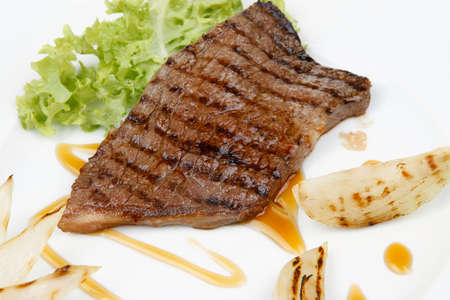 frame less: meat food : roast steak boneless with roast onion, served on green lettuce salad on dish isolated over white background