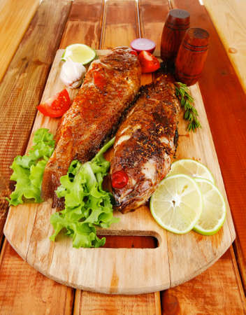 roasted sea fish and castors on wood with tomatoes, lemon and green lettuce salad