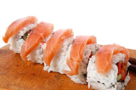sake: onigiri clásico del revés rollos de sushi californiano con salmón en plato de madera aislada sobre fondo blanco con palos Foto de archivo