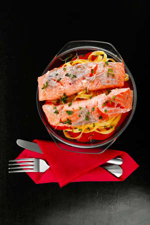 pink salmon: fresh fried natural pink salmon on italian traditional tagliatelles backed with tomato and vegetables served over black wooden table