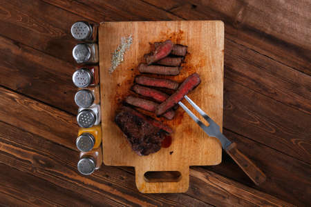 pepperbox: grilled beef fillet steak on fork over wooden board served with different kind of dry spices salt crushed black pepper hot baked sweet paprika red hot chili on dark table