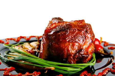 adn: roast red beef meat bbq bloc served on black plate  with green chives adn red hot pepper on black plate isolated over white background