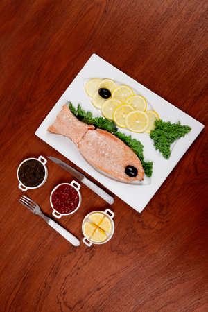 red  fish: healthy food fresh roast red fish salmon with kale lemon antipesto ketchup sauce on white plate over wooden table