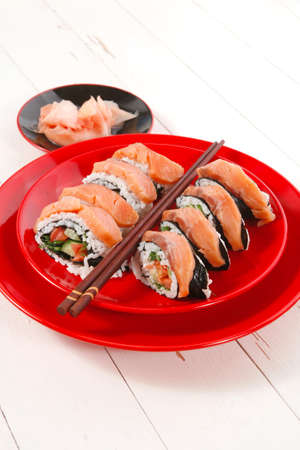 californian: japanese cuisine onigiri sashimi inside out sushi rolls with ginger and sake cup on red plate over white wooden table