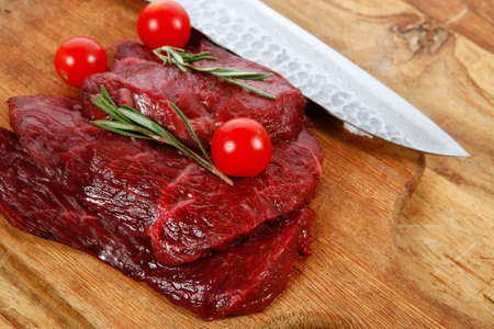 fresh raw beef steak with cherry tomatoes rosemary twig on wood cut plate over table with japanese layered stainless steel knife
