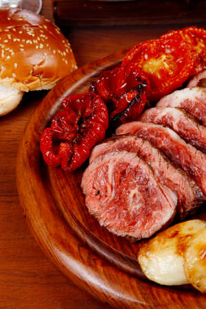 fresh roast bbq beef meat ribeye steak on wooden plate served with tomato juice in wooden cup, boiled broccoli, baked tomatoes and potatoes, with white bun, and red wine glass on light walnut wooden table Stock Photo