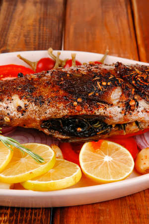 fryed: healthy lunch : whole fried sea sunfish on wooden table with lemons peppers and tomatoes and rosemary twig