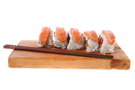 californian: classic onigiri inside out californian sushi rolls with salmon on wooden plate isolated over white background with sticks Stock Photo