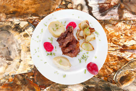 trinchante: beef bourguignon in wine with artichoke and marinated vegetables on white plate isolated over white background Foto de archivo