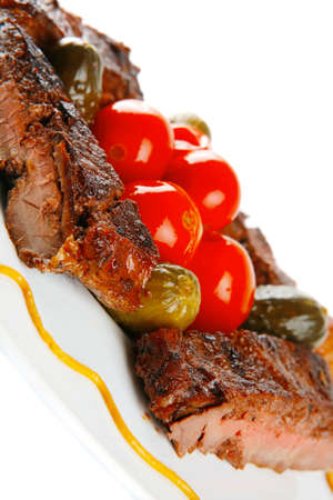 roast beef meat steak with cherry tomatoes and salted cucumbers on white plate isolated over white background Stock Photo