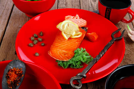 delicious portion of fresh roast salmon fillet on red plate with green salad kale tomato soup bbq sauce and black coffee over wooden table - healthy food, diet cooking concept kale tomato soup bbq sauce and black coffee over wooden table - healthy food, d Stock Photo