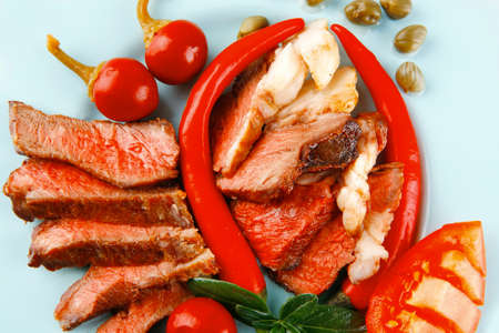 lean over: bacon meat slices served with tomatoes capers and red hot chili peppers on blue plate isolated on white background Stock Photo