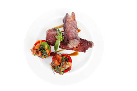 nightime: fresh red beef meat steak barbecue garnished vegetable salad and basil  in half of pepper bell on white plate isolated over white background Stock Photo