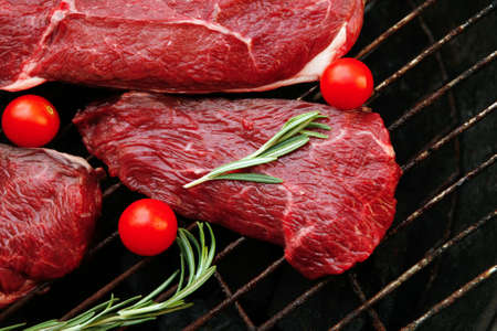 circular muscle: fresh raw beef steak with cherry tomatoes rosemary twig and red pepper bell on black bbq grill ready to prepare Stock Photo