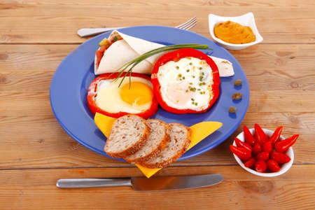 caper: fried eggs and tortilla with salad , red hot pepper and mustard, served on blue plate with cutlery over wooden table in restaurant Stock Photo
