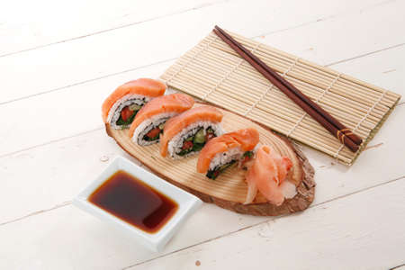 californian: onigiri sushi salmon rolls with soy sauce on wooden plate and bamboo mat on white table with sticks Stock Photo