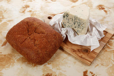 stilton: aged italian deli fresh blue stilton cheese and rye ciabatta served on wooden cutting plate on used baking paper as background Stock Photo