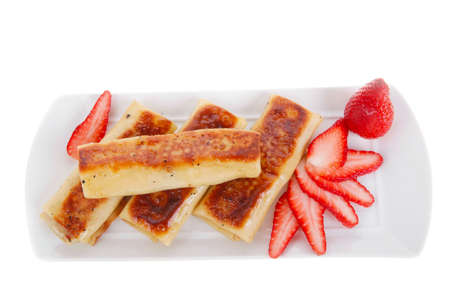 russian food: russian food - cottage cheese wrapped in sweet a pancake with strawberry served on white plate isolated over white