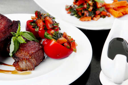 fresh red beef meat steak barbecue garnished vegetable salad and basil on white plate over black wooden table with bbq sauce in sauceboat Stock Photo