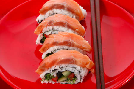inside out: onigiri inside out sashimi shushi with raw salmon and sticks on red plate isolated over white background