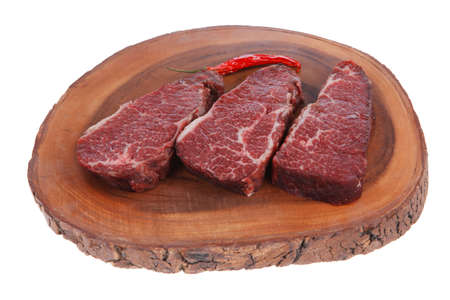 porterhouse: three fresh raw marble beef meat sirloin porterhouse steak on big wooden cutting plate with hot chili pepper isolated on white background