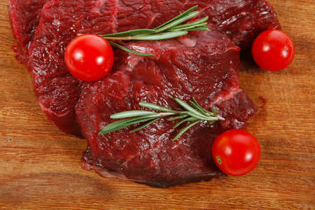 circular muscle: fresh raw beef steak with cherry tomatoes rosemary twig on wood cut board isolated on white background