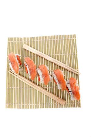 inside out: fresh japan onigiri inside out sashimi sushi on wooden bamboo mat with sticks isolated on white background Stock Photo