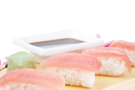 maguro: Nigiri Sushi - Set of Nigiri sushi topped with raw Tuna (maguro) . Isolated over white background . on wooden board