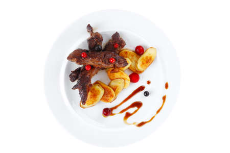 grilled beef meat with berries fried potatoes and cherry under sweet honey sauce on white plate isolated over white background Stock Photo