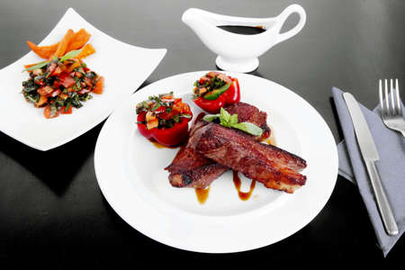 nightime: fresh red beef meat steak barbecue garnished vegetable salad and basil on white plate over black wooden table with bbq sauce in sauceboat Stock Photo