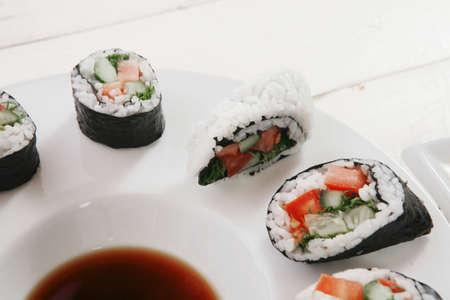 japanese sake: maki uramaki and onigiri sushi rolls with ginger and japan vinegar and sticks on plates over white wooden table Foto de archivo