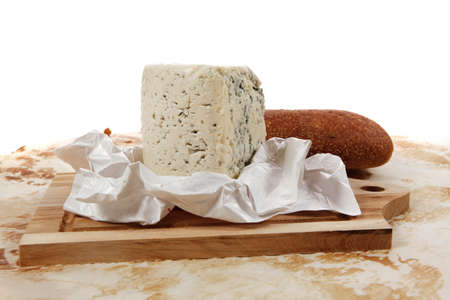 aged italian deli fresh blue stilton cheese and rye ciabatta served on wooden cutting plate on used baking paper as background Stock Photo