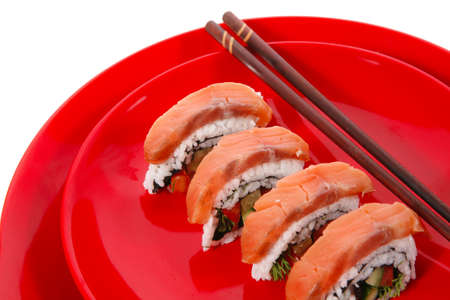 californian: onigiri inside out sashimi shushi with raw salmon and sticks on red plate isolated over white background