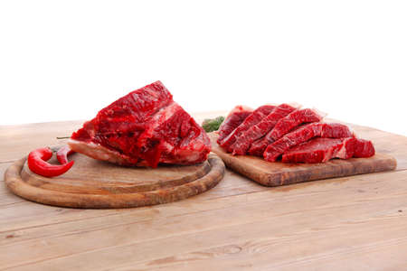 fresh raw beef meat steak and chunk with red hot pepper and dill on wooden cut plates over table Stock Photo