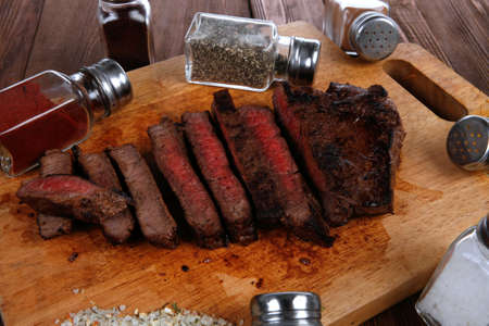 pepperbox: fresh roast red beef meat fillet mignon cutted on wooden plate with many different kinds of dry spices red hot paprika crushed black pepper salt dry mustard grains over table Stock Photo