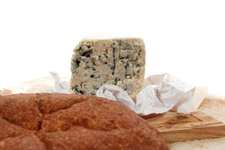 tabla de quesos: aged italian deli fresh blue stilton cheese and rye ciabatta served on wooden cutting plate on used baking paper as background Foto de archivo