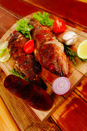 healthy food: two fried sea bass fish served with tomatoes and vegetables on big wooden board over table Stock Photo