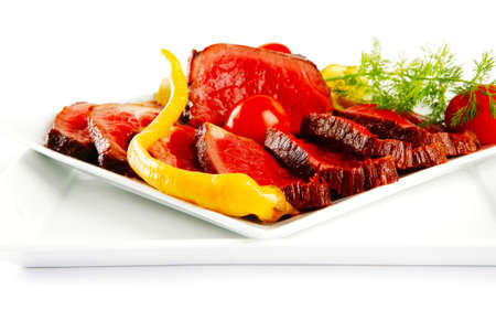 grilled beef meat entrecote on white plates with peppers and tomato isolated on white background Stock Photo