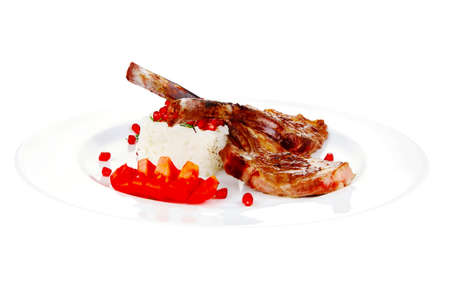 main course: grilled ribs with rice and tomatoes on white plate over white background Stock Photo