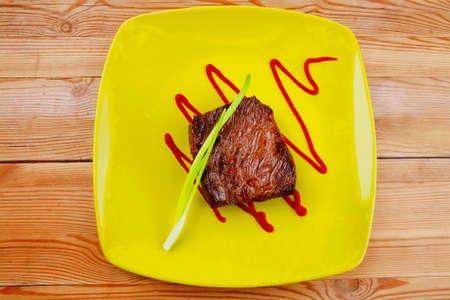 meat food : roasted fillet mignon on green plate with chives and ketchup over wooden table Stock Photo