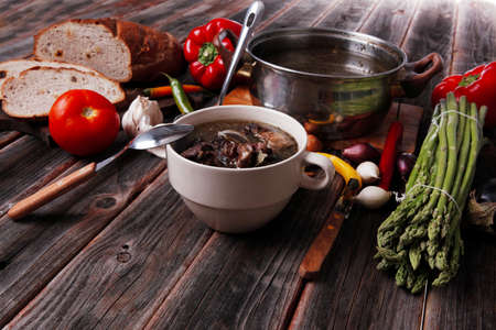 home style beef meat soup vintage country wood table asparagus pepper bell spices bread garlic cutlery eggplant Archivio Fotografico