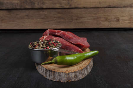 fresh raw beef piece fillet on middle size wooden plate with pepper and peppercorns in measuring spoon space for text on black background Imagens