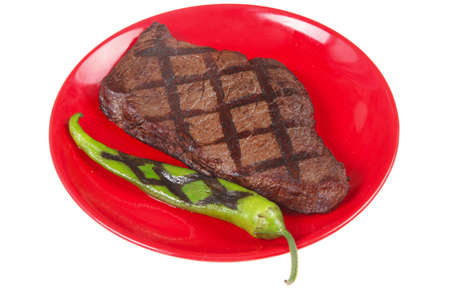 fresh grilled bbq roast beef steak on red plate with green chili pepper isolated on white background