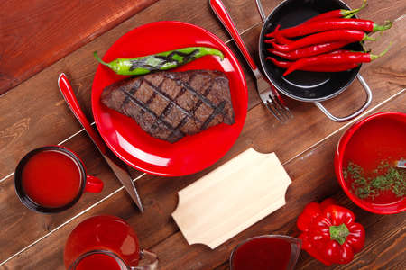 red theme lunch : fresh grilled bbq roast beef steak on red plate with green chili tomato soup ketchup sauce paprika small jug glass ground pepper american peppercorn and modern cutlery served on wooden table with empty nameplate Stock Photo
