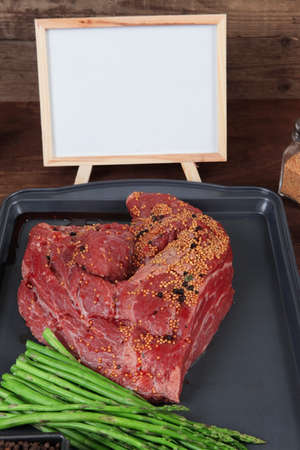 meat raw beef fillet chunk on black tray asparagus on wooden plate allspice pink peppercorn mustard nametable  empty space for text