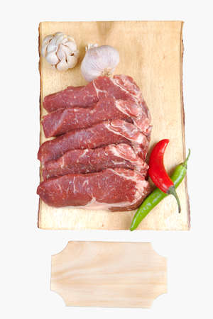 sirloin sinta fillet sliced on wooden plate with garlic and green red hot pepper isolated over white background with white empty menu plate for text near Stock Photo