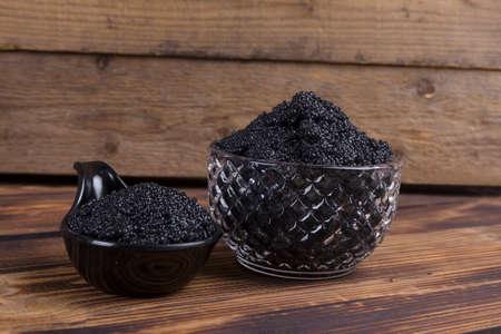 fresh raw black sturgeon hausen caviar in white crystal bowl on wooden background 스톡 콘텐츠